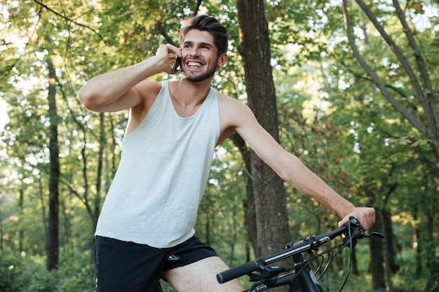 Сyclist talking on the phone in forest