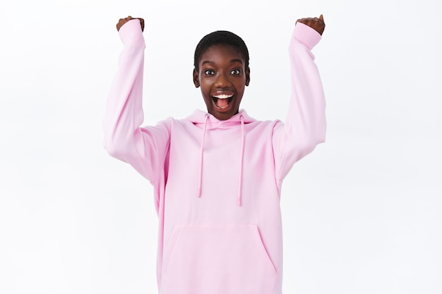Sì congratulazioni. divertito e felice carina ragazza afroamericana che vince, pompa a pugno e sorridente, ascolta fantastiche notizie fantastiche