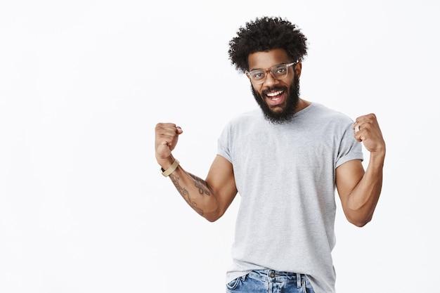 예, 용기와 성공을 달성할 준비가 되어 있습니다. 자신감 있고 기뻐하는 낙천적인 아프리카계 미국인 수염 난 남자가 축하의 의미에서 주먹을 꽉 쥐고 좋은 결과에 만족하고 있다