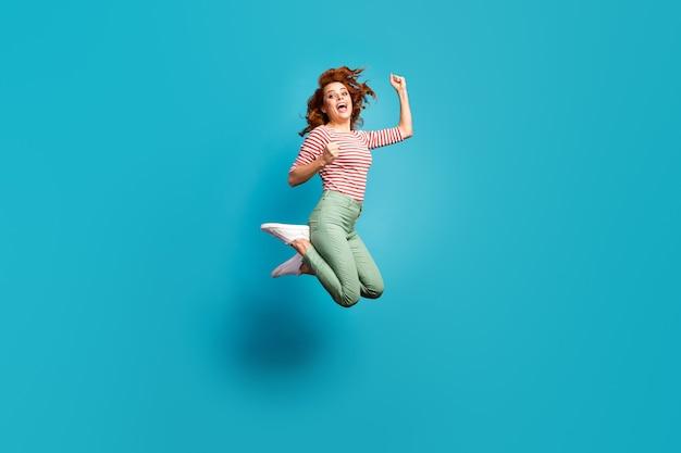 Да! полное фото профиля смешной женщины прыгать высоко, чувствовать сумасшедшие эмоции, поднять кулаки, выиграть соревнование, носить повседневную красную белую рубашку, зеленые брюки, изолированную обувь, синий