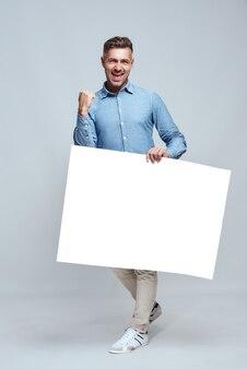 Да во весь рост красивый бородатый мужчина в повседневной одежде держит одну руку сжатой в кулак и держит пустую пустую доску, стоя на сером фоне. победа. реклама