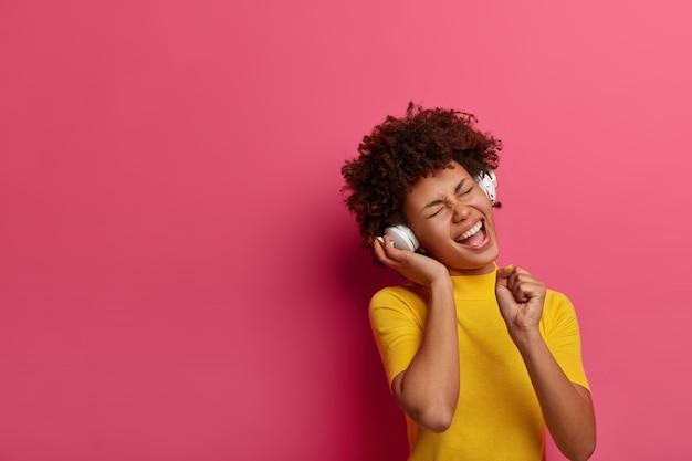 Да отличный звук. обрадованная кудрявая женщина слушает звуковую дорожку в наушниках, сжимает кулак, как держит микрофон, держит глаза закрытыми, носит желтую футболку, дрожит от хорошей энергии, изолирована на розовой стене
