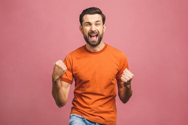 Да! счастливый победитель! счастливый молодой красивый человек показывать и держа рот открытый пока стоящ против розовой стены.