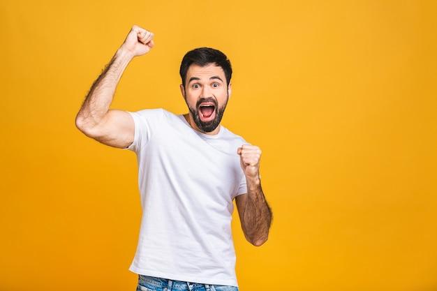 うん!幸せな勝者!黄色の背景の上に孤立して立っている間、身振りで示すと口を開いたままにしておく幸せな若いハンサムな男。