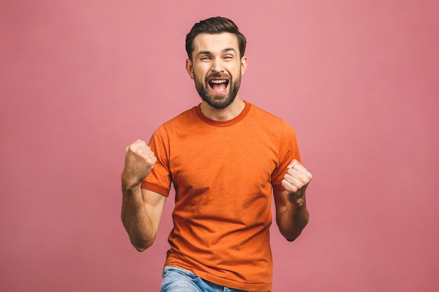 Yeah! happy winner! happy young handsome man gesturing and keeping mouth open while standing against pink wall.