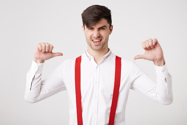 Yeah, i am a winner! self-confident young guy did something significant, wants to receive looks happy pointing on himself with thumb, feels like a winner, leader, successful man, wearing a white shirt