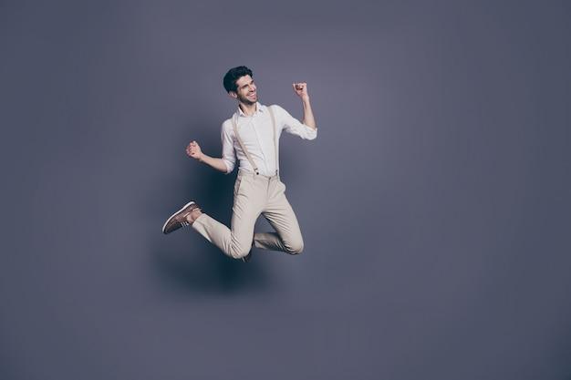 Да я получаю доход! довольный веселый профессиональный парень слышит, как он выиграл денежную лотерею, прыжок, поднять кулаки, крик: да, да, носить современную одежду.