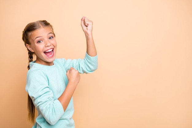 Yeah! profile photo of beautiful excited little lady ambitious raise fist celebrate success astonished ecstatic wear blue pullover isolated beige pastel color wall