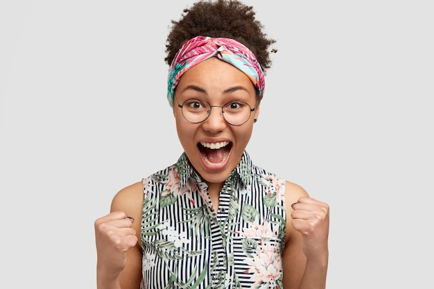 Yeah, that`s wonderfull! shot of glad african american female with crisp hair, screams with happiness, clenches fists, makes winning gesture, achieves everything in life, wears elegant blouse