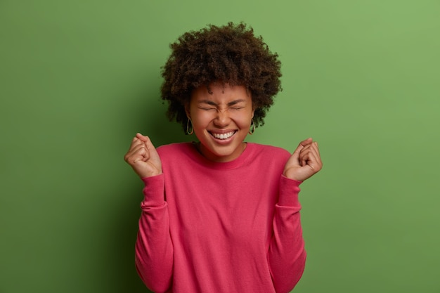 ええ、これは私の機会です。うれしそうなアフロアメリカ人女性は成功を喜び、勝利で拳を食いしばり、勝利を望んでおり、達成を祝い、バラ色のセーターを着て、緑の壁に隔離されています