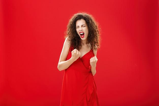 Да мы чемпионы. торжествующая счастливая и восхищенная богатая элегантная женщина с вьющимися волосами в стильном платье, сжимая кулаки в жесте «да», крича радостно празднуя победу или победу над красной стеной.