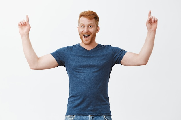 Yeah we are winners. portrait of joyful celebrating male with ginger hair, bending and raising index fingers up in triumph gesture, grinning from happinesss and satisfaction, rejoicing from good news