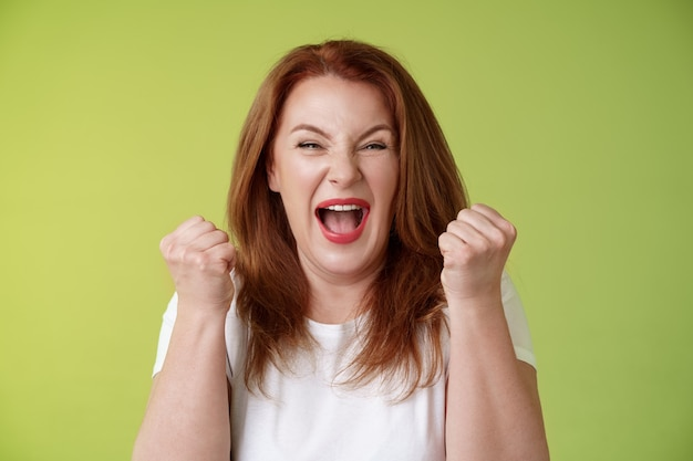 Yeah we did it joyful lucky redhead middleaged female winner pump fists up celebration success gesture yelling triumph joy smiling broadly celebrate awesome news stand green wall happy
