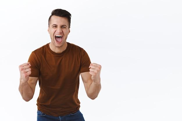 네, 우리가 해냈습니다. 성공적인 행복하고 의기양양한 잘생긴 남자는 그의 팀이 득점한 것을 보고 기뻐하며 스포츠 tv 게임을 시청합니다