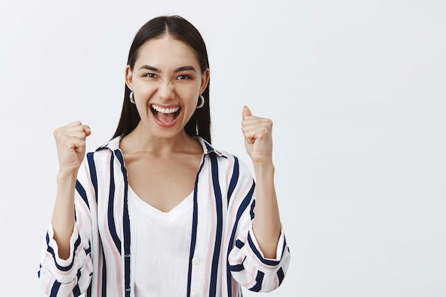Yeah we did it. triumphing happy enthusiastic woman in striped blouse, lifting clenched fist and saying yes while celebrating successful deal or victory, being pleased and thrilled over gray wall