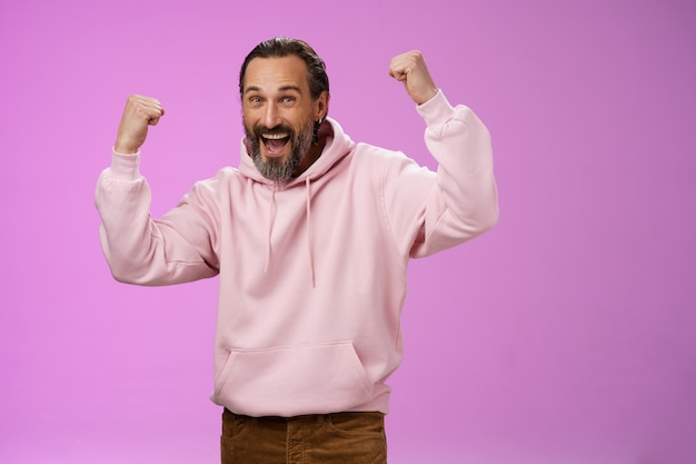 Yeah who cares age. carefree delighted happy old man bearded in trendy pink hoodie raise fists joyfully triumphing having fun glad win celebrating success accomplish goal, posing purple background.
