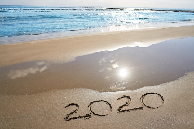 Year 2020 numbers spell written on beach
