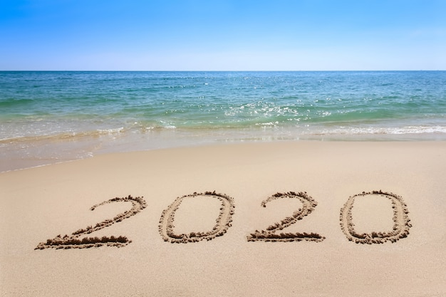 Year 2020 written at the sand beach with sea wave water