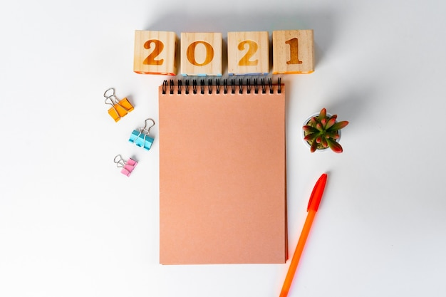 Цифры 2022 года и канцелярские товары на белом столе