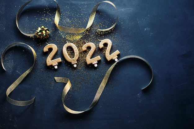 The year 2022 written with golden candles and two sparkling champagne glasses on a black background