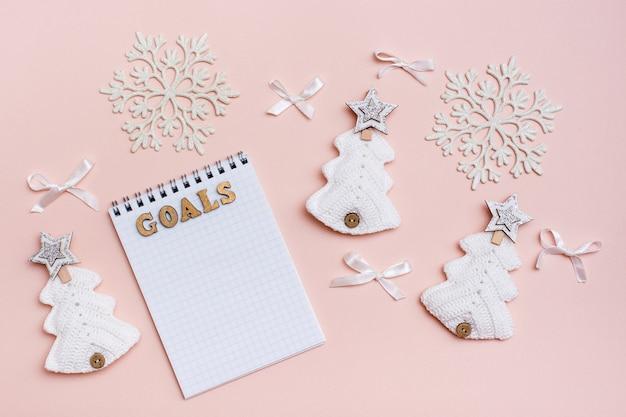 Цели года. блокнот и рождество ручной работы на пастельном фоне. вязаные елки