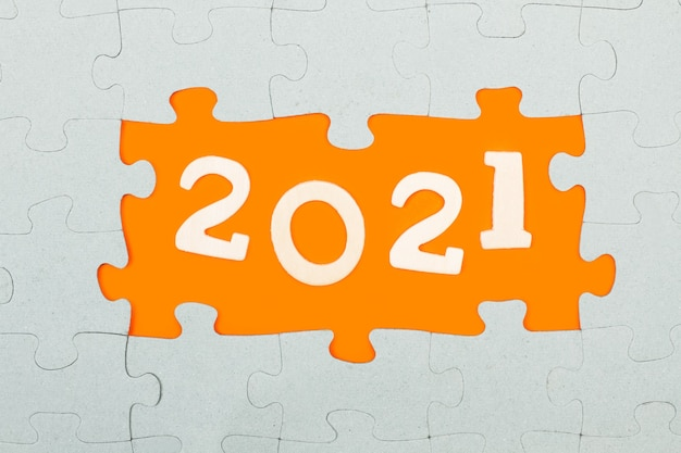 Year greeting with puzzle pieces on a orange background