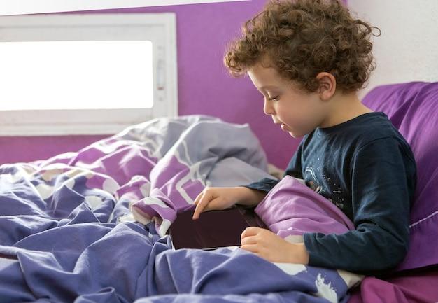 Летний мальчик с вьющимися волосами сидит на кровати с планшетом в руках и играет