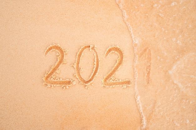 2021年は、黄色い砂のクローズアップの砂浜に刻まれています。海の波が碑文2021を洗い流します。年の変化の概念。