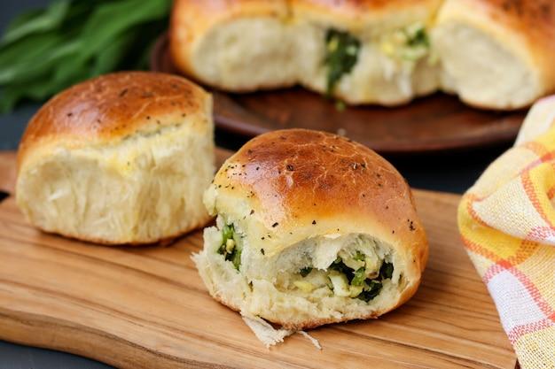 녹색과 삶은 계란으로 채워진 효모 빵은 어두운 배경에 대해 나무 판자에 있습니다