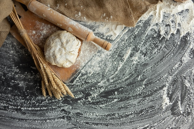 Yeast dough on the table with a rolling pin and ears of wheat. flour scattered on the table.