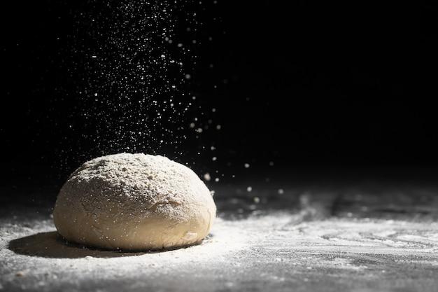 暗い背景に小麦粉を注ぐ酵母生地