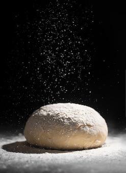 暗い背景に小麦粉を注ぐ無酵母生地