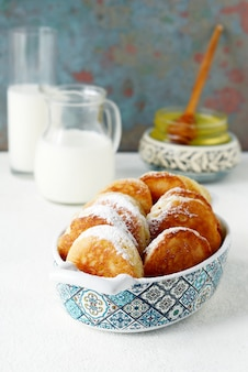 Yeast pancakes in powdered sugar with milk and honey
