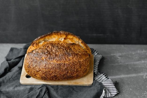 イーストフリーのサワードウパン美しいヨーロッパの女性パン屋が手にパンを持ってパンを焼く