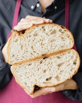 イーストフリーのサワードウパン美しいヨーロッパの女性パン屋が彼女の手にパンを持っています