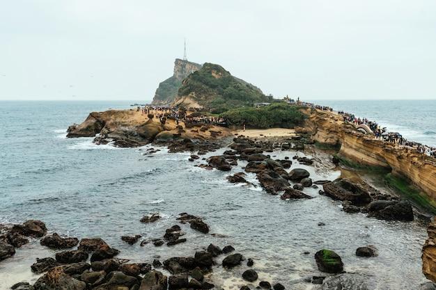 Разнообразие с высоты птичьего полета туристов, идущих в yehliu geopark, мыс на северном побережье тайваня. пейзаж соты и грибных скал, разрушенных морем.