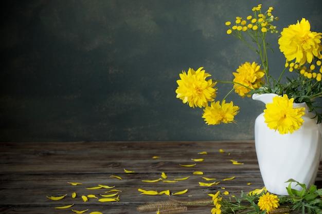 暗い背景に白い水差しのyeliow花
