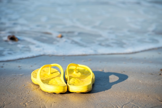 タイ、クラビのアオナンにある波の激しいビーチでのビーチサンダルや靴。晴れた日の夏の休日旅行のコンセプトを楽しむための砂の上のサンダル。