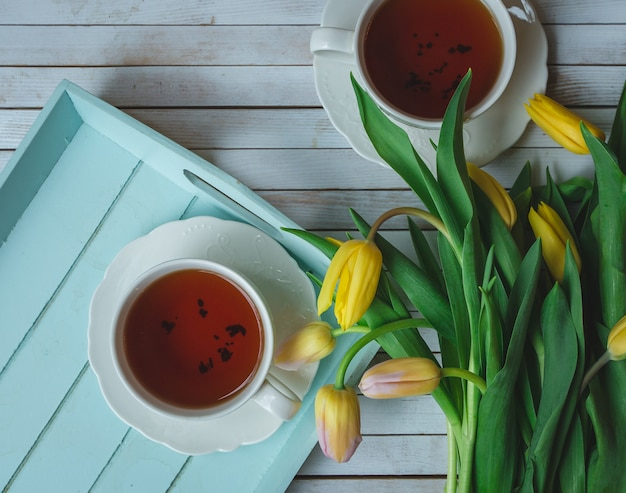 Yello тюльпаны и две чашки черного чая