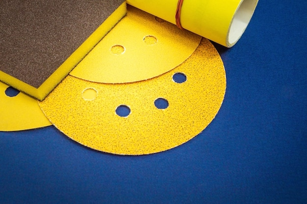 Yellow abrasive tools and sandpaper on blue background