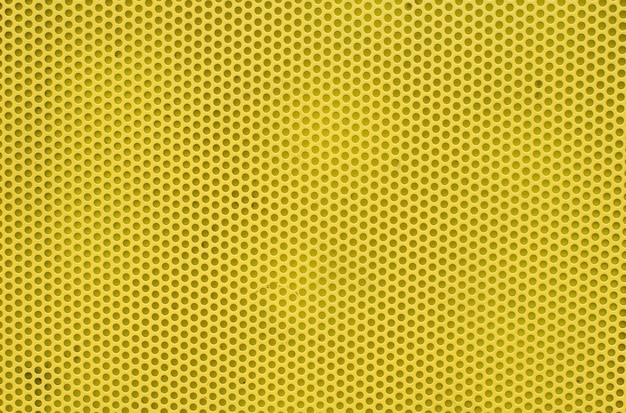 Yellow abstract background on based of metal, texture of the yellow surface with a lot of round holes.