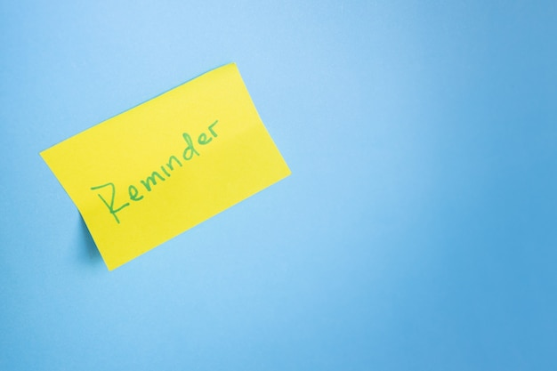 Yellow adhesive note on blue light background minimalist concept copyspace