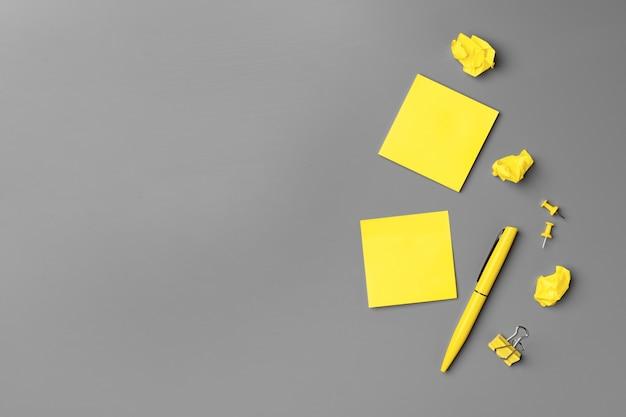 Желтые клейкие заметки и ручка на сером фоне крупным планом