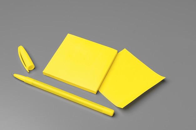 黄色の粘着ノートと灰色のペンをクローズアップ