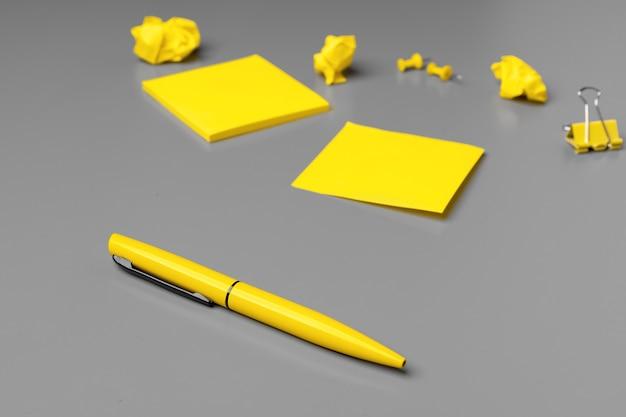 灰色の表面に黄色の粘着ノートとペン