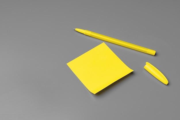 黄色の粘着ノートと灰色のペン