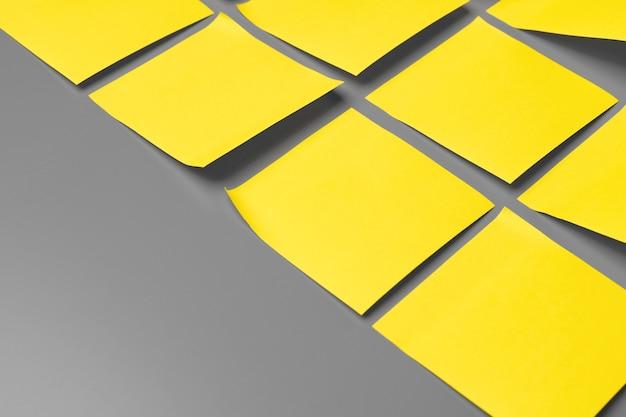 灰色の背景に黄色の粘着メモがコピースペースをクローズアップ