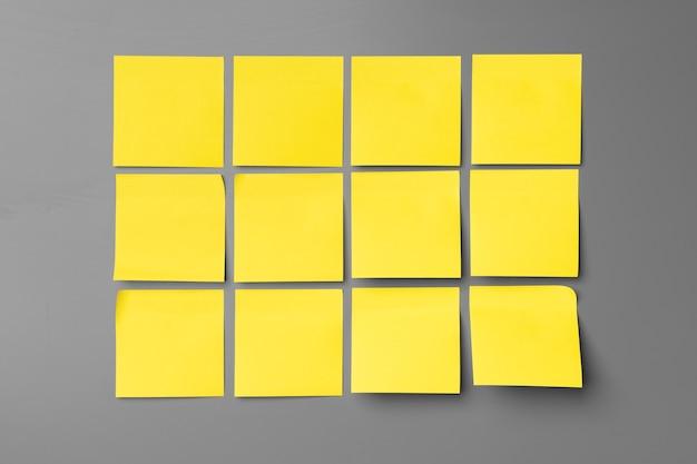 灰色の黄色の粘着ノートはコピースペースを閉じます
