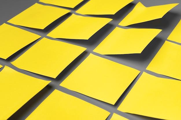 Желтые клейкие заметки на сером крупным планом