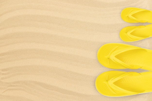 Yellow adults and childrens flipflops on the beach top view